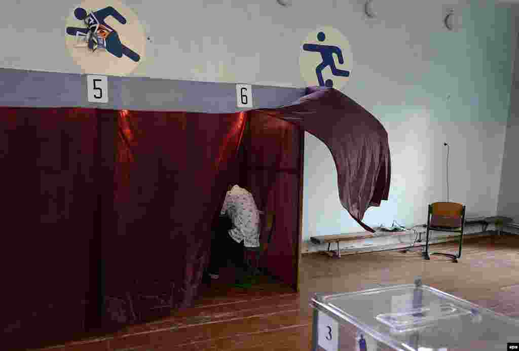 A voter prepares his ballot in a voting booth set up in a gym of the Novospasskoye village in Dnipropetrovsk, some 400 kilometers southeast of Kyiv, Ukraine, on May 25. (epa/Filip Singer)