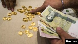 A customer buys Iranian gold coins at a currency exchange office in Tehran's business district.