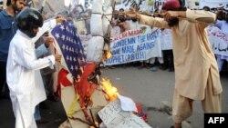 Протестующие в Пакистане попирают флаг США.