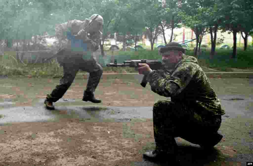 Pro-Russia militants fire at Ukrainian border guards defending the Federal Border Headquarters in Luhansk on June 2. (AFP/Sergei Gapon)