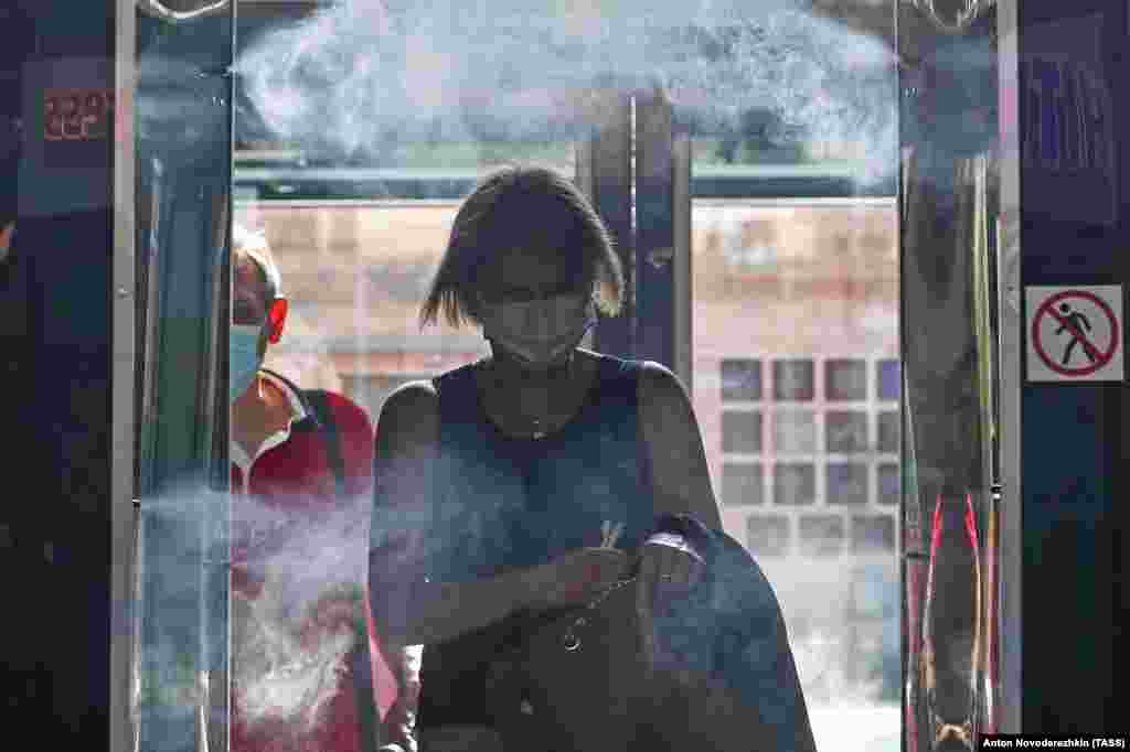 A woman walks through a disinfection gate at the entrance to a food court in Moscow on June 16.
