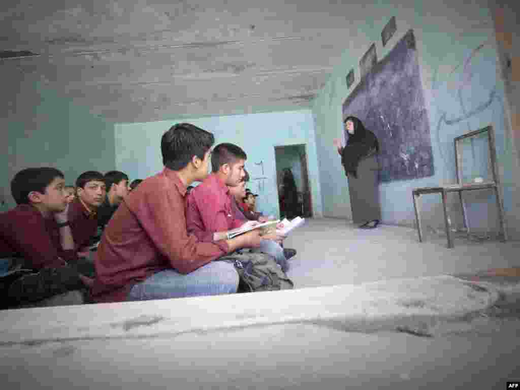 Afghan students sit on the floor during a lesson at the Nasoana school in Kabul.