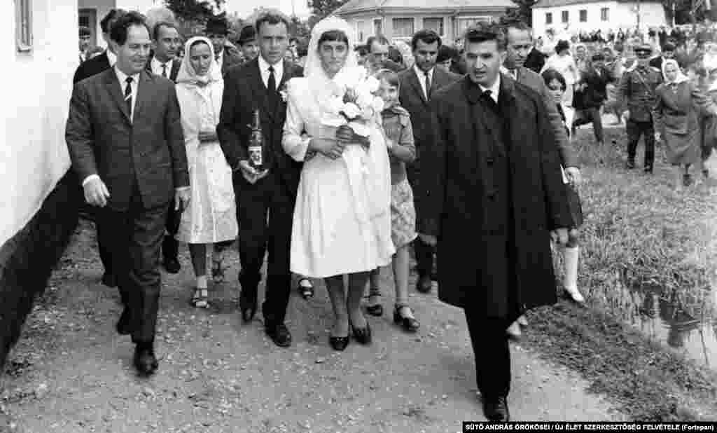 Nicolae Ceausescu walks with a newlywed ethnic Hungarian couple near Brasov in 1967. Although Ceausescu oversaw the widespread repression of his political opponents, he was initially relatively popular with Romanians -- especially after he took out foreign loans that ensured Romanian shops were well stocked with food.