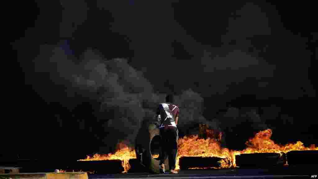 A Shi'ite protester sets tires on fire during clashes with police following a demonstration in solidarity with jailed Bahraini human rights and political activists in the village of Sitra. (AFP/Muhammad al-Shaikh)