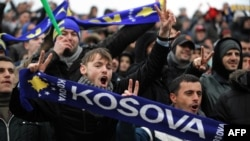 "Supporters of the Kosovo soccer team holding scarves reading ""Kosovo"" cheer in the stands during a friendly match between Kosovo and Haiti in Mitrovica in March 2014."