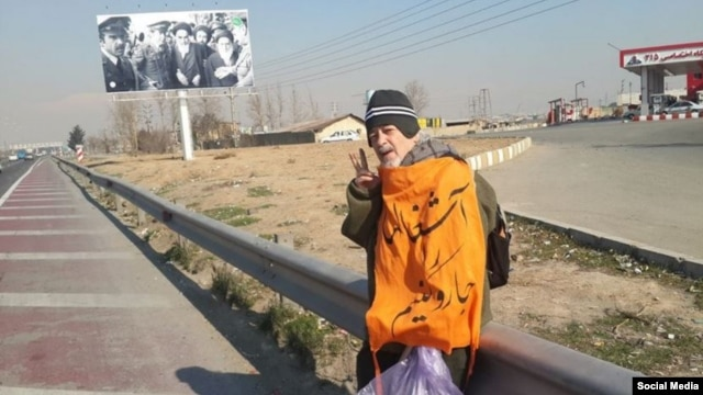 "Mohammad Maleki, wearing a shawl that says ""Let's Sweep Garbage,"" flashes the victory sign along a roadway outside the capital, where he and a colleague were dumped by security agents."