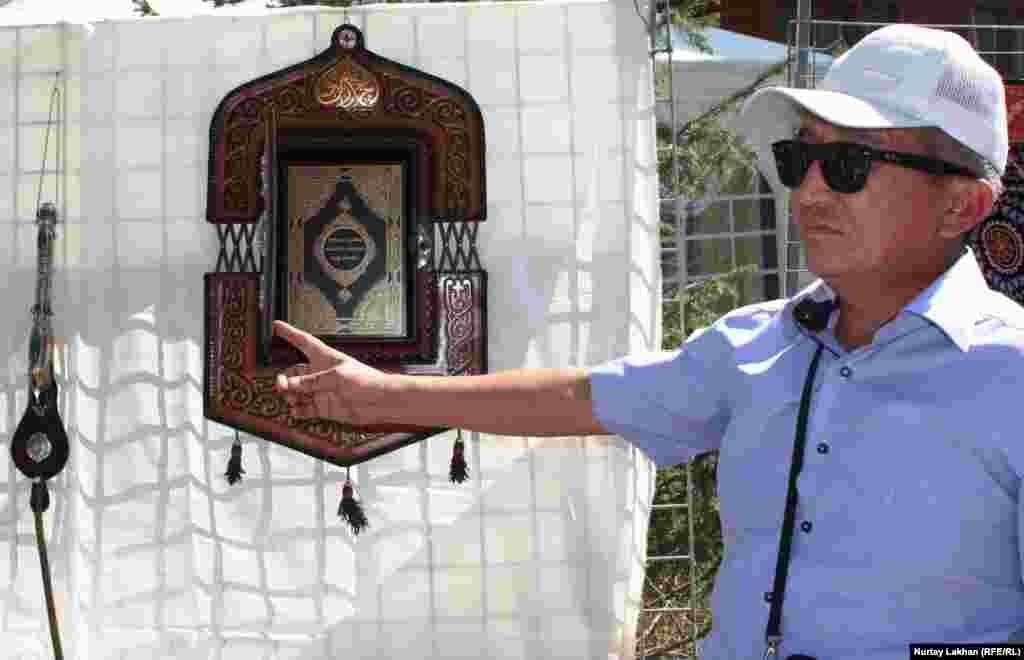 Оңтүстік Қазақстан облысынан келген шебер Мирлан Мамбетакунов Құран кітабына арнап жасаған қапты көрсетіп тұр.