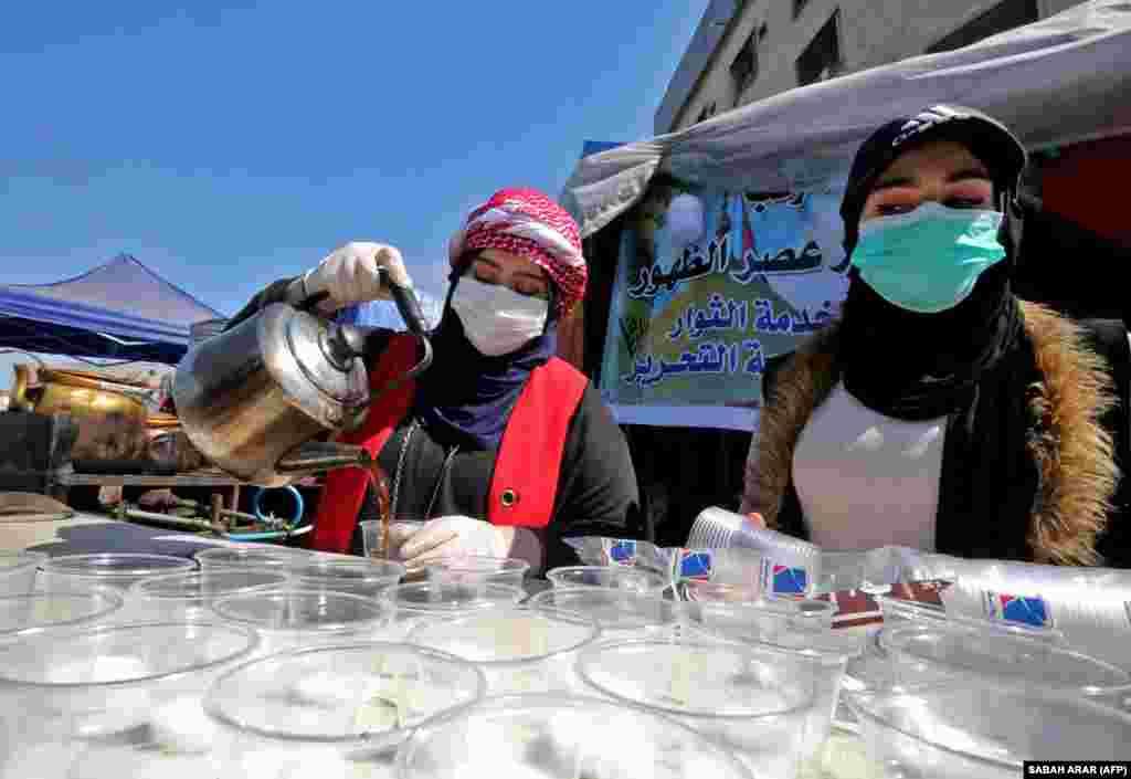 Бағдадтағы Тахрир алаңында билікке қарсы наразылық білдіріп отырғандарға шай құйып жатқан әйелдер. 4 наурыз 2020 жыл.