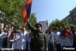 Мужчина в военной форме с флагом Армении в руке во главе марша студентов в центральной части Еревана. 23 апреля 2018 года.