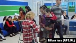 Безработные оставляют резюме и получают брошюры от потенциального работодателя на ярмарке вакансий в Шымкенте. 18 апреля 2015 года. Иллюстративное фото.
