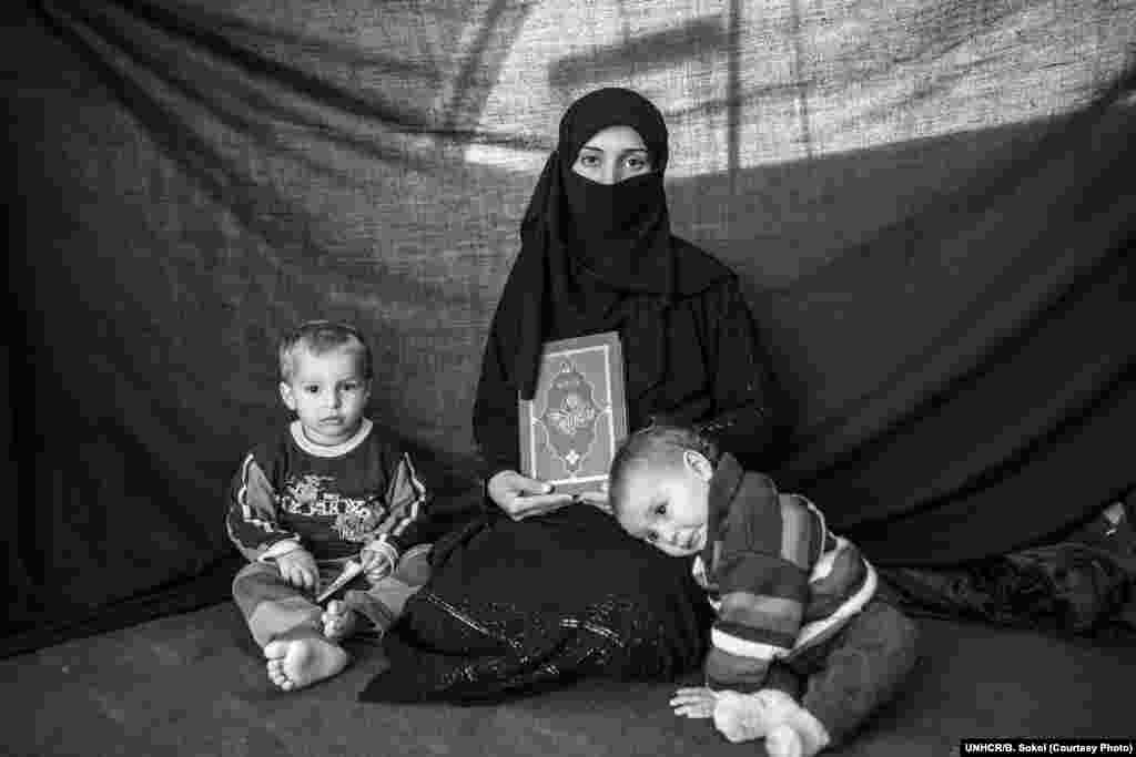 Iman*, 25, poses for a portrait with her son Ahmed, 2, and daughter Aishia, 1, in Nizip refugee camp, Turkey, on 4 December 2012. They arrived in Nizip ten weeks before this photograph was taken, after fleeing their home in Aleppo. After weathering months of conflict, Iman decided it was time to flee when she heard accounts of sexual harassment against women in Aleppo. Iman lost five family members, and the home where they were taking shelter was destroyed in a ferocious attack. The most important thing Iman was able to bring with her is the Koran she holds in this photograph. She says that religion is the most important aspect of her life, and that the Koran inspires a sense of protection.
