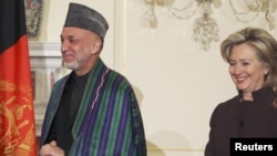 U.S. Secretary of State Hillary Clinton (right) walks with Afghan President Hamid Karzai before the expanded bilateral meeting at the State Department in Washington on May 11.