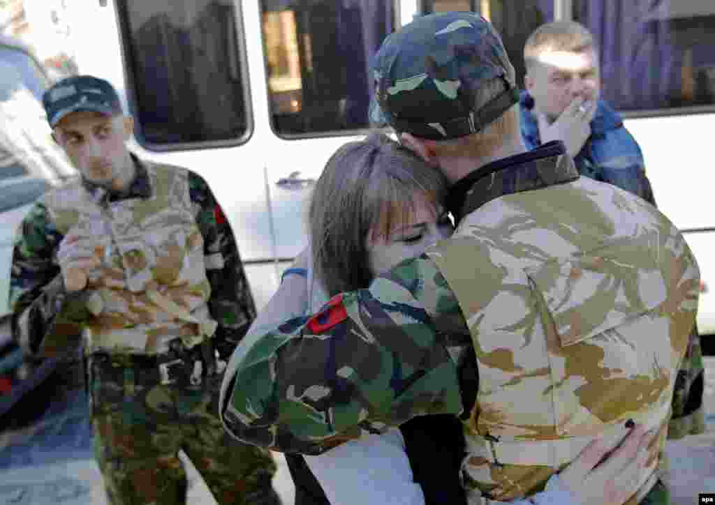 A young Ukrainian volunteer and member of the Maidan self defense forces is embraced by his girlfriend on Kyiv's Independence Square before his deployment at a training facility.