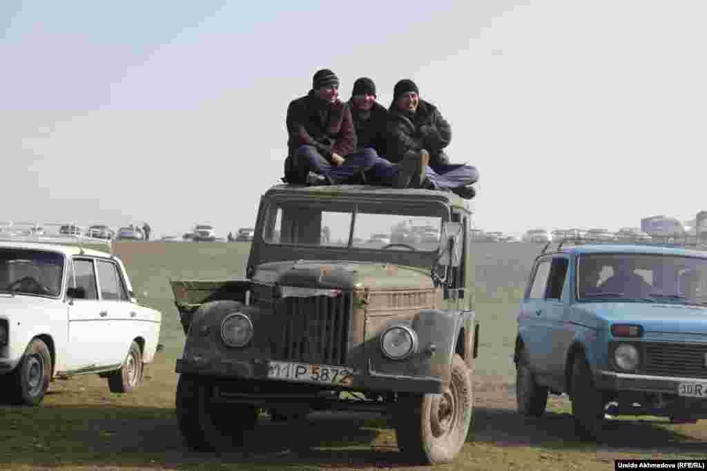 Зрители сидят на крыше старого советского джипа.