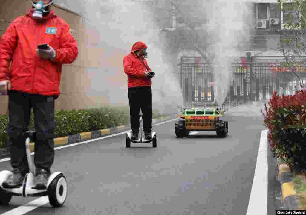 Робітники в захисних масках слідкують за роботом, який розпилює дезінфікуючий засіб у житловому комплексі в Ухані