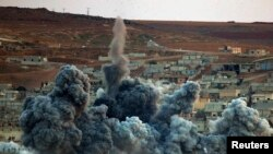 Syria -- An explosion following an airstrike is seen in the Syrian town of Kobani, October 2, 2014