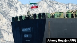 An Iranian flag flies on the oil tanker Adrian Darya 1, previously named Grace 1, as it sits anchored after authorities in the British territory lifted their detention order in mid-August.