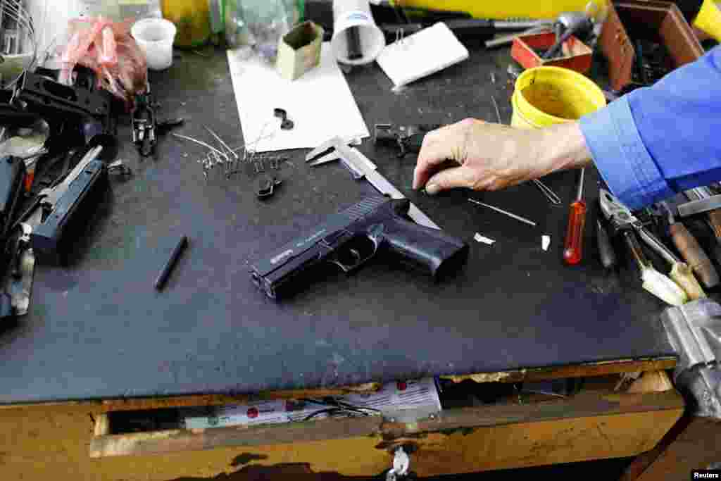 A weapons designer picks up a prototype of a handgun in the manufacturing hall of Zastava Arms.