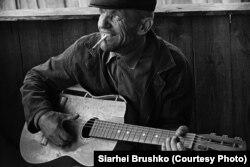 Мужчына паліць цыгарэту і грае на гітары, фота Сяргея Брушко