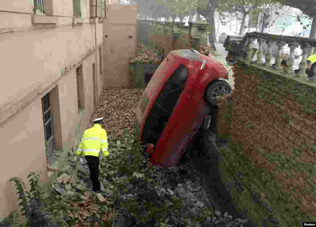 A policeman looks at a car that fell into a pit after crashing through a brick wall on a hazy day in Xianyang, Shaanxi Province, China. Local police said the accident occurred when the driver could not see the road clearly due to thick fog. No one was injured. (Reuters)