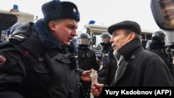 Russian human rights activist Lev Ponomaryov (right) speaks with a police officer during a rally in front of the FSB headquarters in central Moscow on March 14.