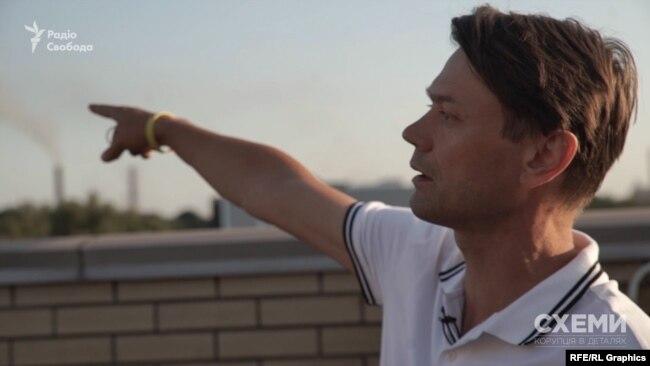 Депутат Кам'янської міськради Андрій Іванченко з даху показує підприємства, через які місто вкриває димом