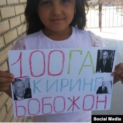 A young girls holds up a sign saying she hopes the Uzbek president lives to be a hundred.
