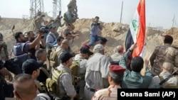 Премьер-министр Ирака поднимает флаг над освобожденной от «ИГ» территорией.