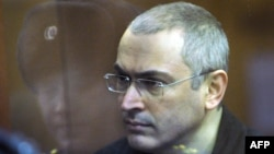 Former Yukos oil company chief executive officer Mikhail Khodorkovsky stands behind a glass wall at a courtroom in Moscow, 29Dec2010