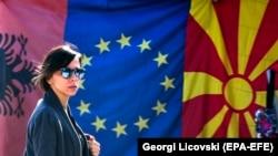 Албания, Евробиримдик жана Түндүк Македониянын желектеринин жанынан өтүп бараткан аял. Скопье, 3-февраль, 2020-жыл.