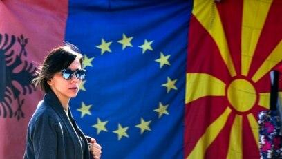 Žena prolazi pored zastava Albanije, EU i Severne Makedonije na pijaci u Skoplju, 3. februara 2020.