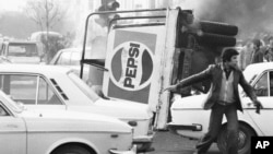 IRAN -- file -- In this Dec. 27, 1978 file picture, an overturned truck with a Pepsi soft drink logo burns in the center of Tehran during riots which paralyzed the city. The popular revolt against the shah raised alarm bells in the West, which saw the sh