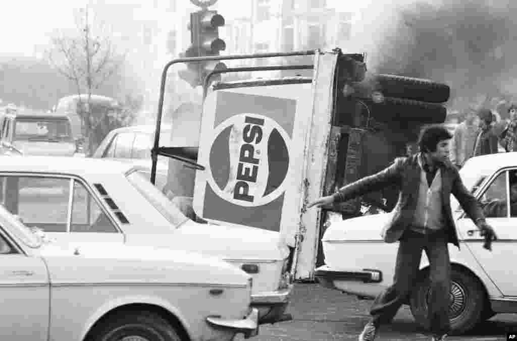 An overturned truck with a Pepsi logo burns in the center of Tehran during riots which paralyzed the city on December 27, 1978.