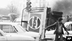 გადაყირავებული სატვირთო მანქანა პეპსის წარწერით იწვის თეირანის ცენტრში. 1978 წლის 27 დეკემბერს არეულობის შედეგად ირანის დედაქალაქი პარალიზებულია.