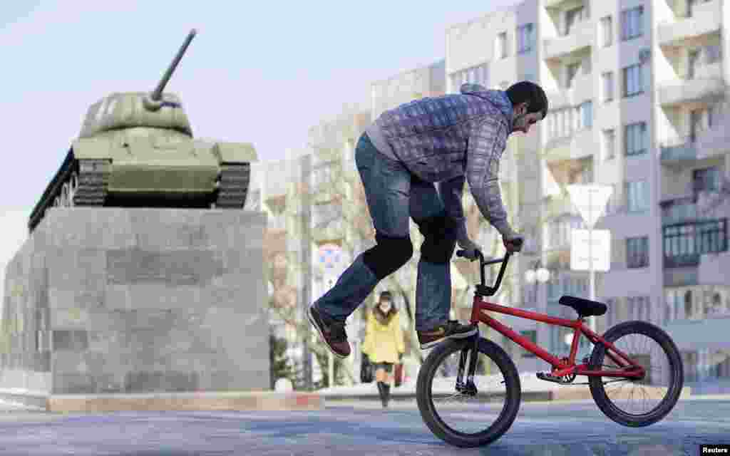 Belarus -- A man performs tricks on his bicycle in front of a World War Two T-34 Soviet tank monument in central Minsk, March 10, 2010