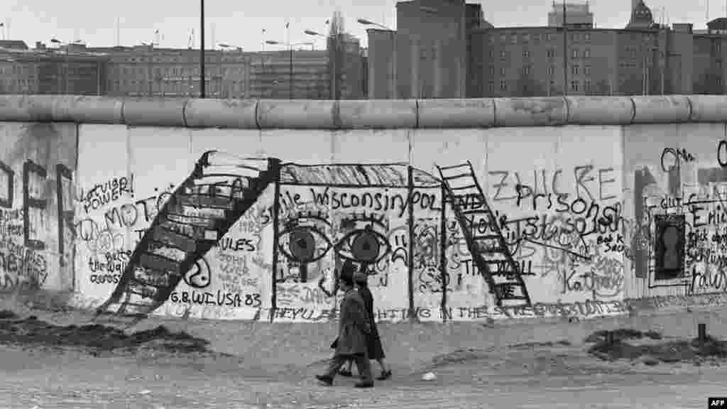 Западная сторона стены стала своего рода картинной галереей– свои граффити и рисунки на ней оставляли художники и туристы со всего мира. Тщательно охраняемая восточная сторона оставалась чистой. (Фото сделано 29 апреля 1984 года)