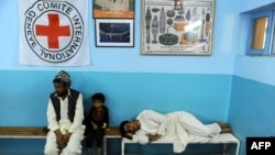 patients wait on a benches at the International Committee of Red Cross ( ICRC) hospital for war victims in Herat province, August 17, 2014.