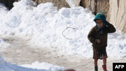 Мальчик в лагере бездомных в Афганистане идет по снегу.