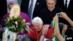 Pope Benedict XVI shakes hands with pilgrims after celebrating a mass in Rome on August 15.