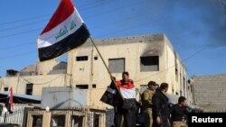 Иракский военный держит флаг в центре Рамади