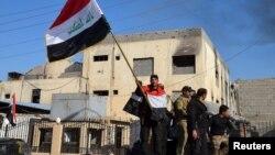 Ирак -- Өкмөттүк башкы имаратка өлкө туусун көтөрүү. Рамади, 28-декабрь, 2015.