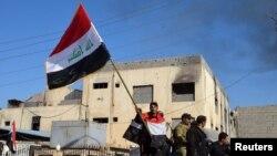 Іракські військові тримають прапор біля урядового комплексу у Рамаді, 28 грудня 2015 року