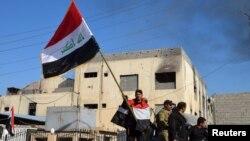 Член иракских сил безопасности держит в руках флаг рядом с правительственным комплексом в городе Рамади, 28 декабря 2015 года.