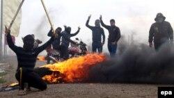مسلحون من الأنبار يشعلون النار في إطارات سيارات على إحدى الطرق قبل أن تشن قوات الأمن العراقية عملية عسكرية في المحافظة.