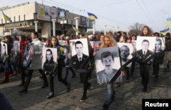 People carry portraits of local residents killed in fighting with pro-Russian separatists during a commemoration rally in Kharkiv on February 22.