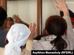 Родственницы подсудимых по делу о событиях в Шетпе здороваются с ними в суде. Актау, 17 апреля 2012 года.