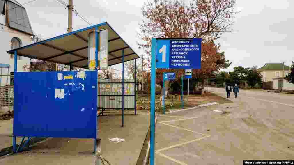 Стара табличка на зупинці. Частина зазначених на ній міст розташовані на материковій частині України
