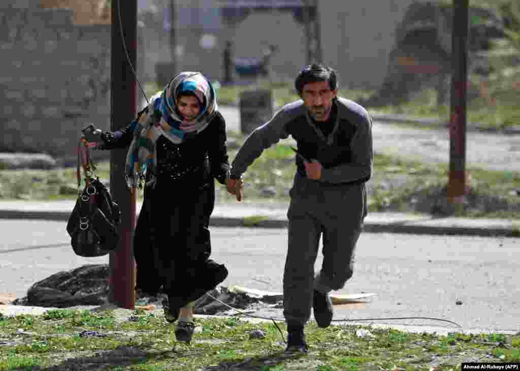 Civilians run for cover as they flee Mosul's Al-Tayaran neighborhood on February 28. According to Reuters, the first thing many civilians ask Iraqi forces for is a cigarette. Smoking was forbidden under Islamic State rule.