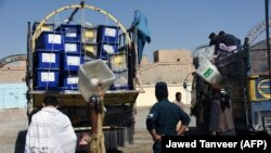 Employees of the Afghan Independent Election Commission (IEC) unload ballot boxes from a turck at a polling centre ahead of legislative election in Kandahar Province on October 26.