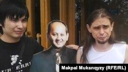 Гражданские активисты Ринат Кибраев (слева) и Дмитрий Щелоков (справа) с фотомакетом оппозиционного политика Мухтара Аблязова у акимата города Алматы. 20 августа 2013 года.